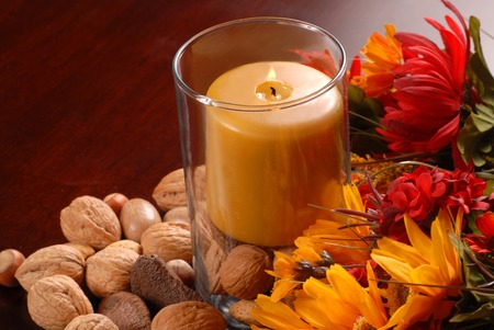 Candle in an autumn setting with nuts and flowers photo
