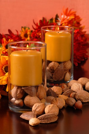 Two candles with nuts in an autumn setting photo