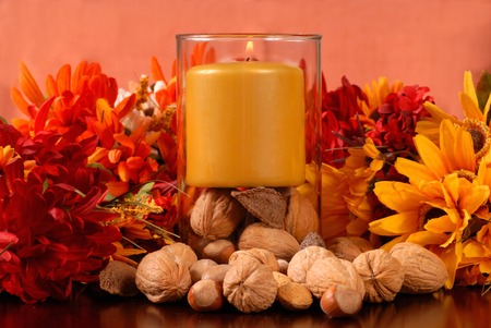 A candle with nuts in an autumn setting photo