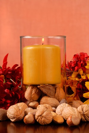 A single candle with nuts in autumn setting photo