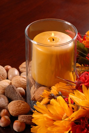 Single candle with nuts in autumn setting photo