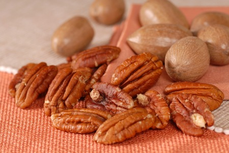 whole pecans: Several whole and shelled pecans on a table