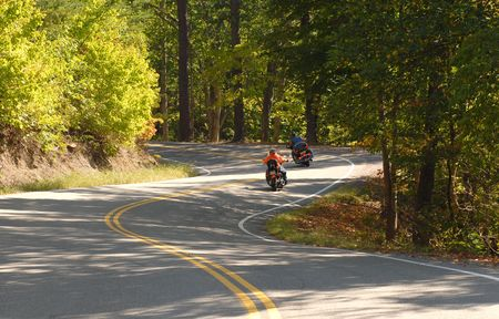 exhilarating: Two motorcyclists driving along a winding road in the forest Stock Photo