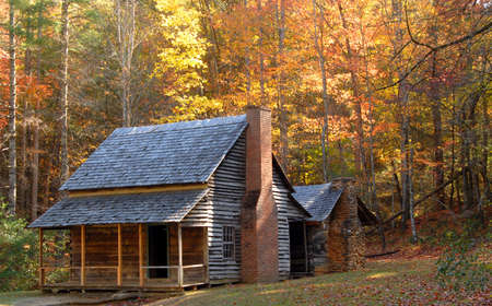 A log cabin in a wooded setting during the autumn season Stock Photo