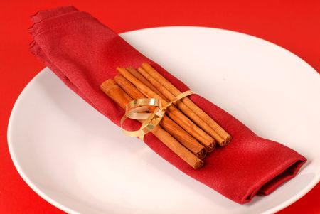 cinammon: Cinammon sticks wrapped in a red napkin on a white plate Stock Photo