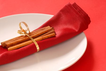 cinammon: Cinammon sticks wrapped on a red napkin with a ribbon
