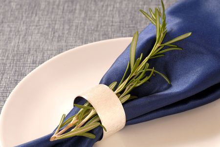 napkin ring: A napkin with rosemary herbs held in place by a silver napkin ring