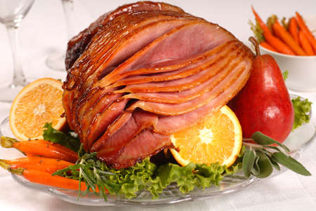 fruit platter: An Easter ham glazed with brown sugar and honey served with carrots, fruit and herbs