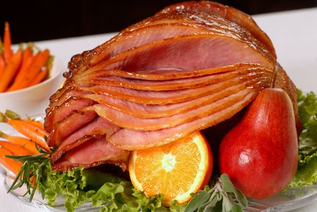 A spiral cut honey glazed Easter ham with fruit and carrots
