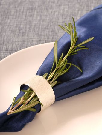 napkin ring: A sprig of fresh rosemary attached to a blue napkin with a silver napkin ring