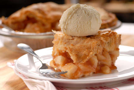 flaky: A piece of freshly made deep dish apple pie with a flaky crust and vanilla ice cream