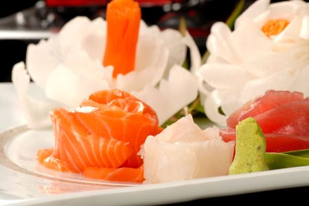 Platter of Asian tuna and salmon sashimi with dicon radish flowers photo