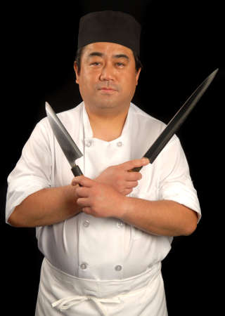 oriental cuisine: Male Japanese sushi chef posing with knives Stock Photo