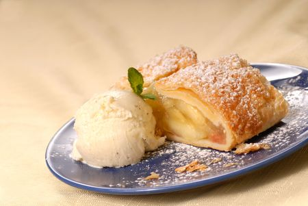 Freshly baked apple strudel with vanilla ice cream and mint dusted with powdered sugar