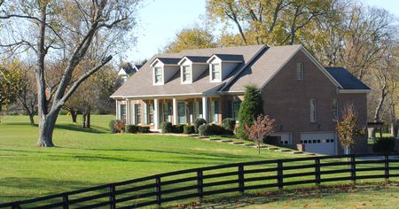 housing lot: Beautiful elegant home with a rail fence on a large piece of property