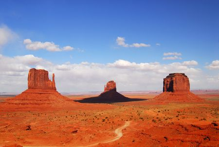 Three large rock formations and road found the the Navajo nation land of Monument Valley photo