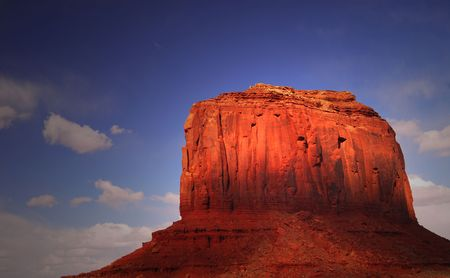 Large rock formation being struck by dramatic lighting in the Navajo nation land of Monument Valley photo