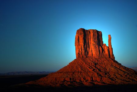 Dramatic light of dawn striking a rock formation in the Navajo nation land of Monument Valley photo