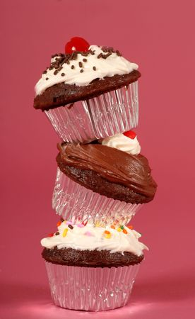 Three delicious chocolate cupcakes with buttercream frosting stacked on their edges photo