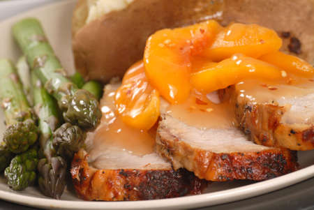Grilled pork tenderloin with peach sauce and asparagus