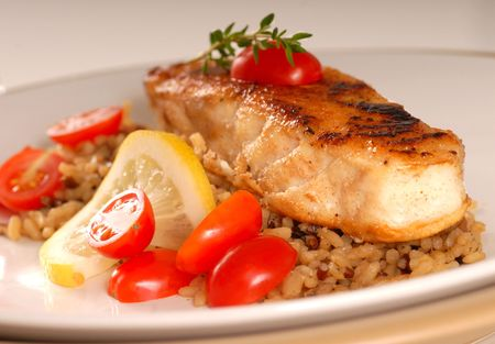Fresh halibut seared with tomato, lemon and thyme on a bed of brown rice