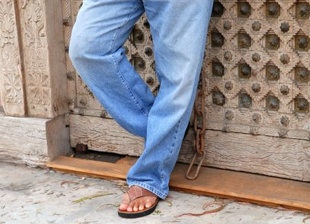 sandels: Man standing against a door from the legs down wearing blue jeans
