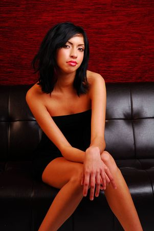 pouty: Attractive young latino woman wearing a sexy dress while sitting on couch