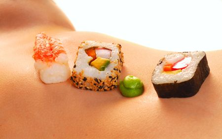 Several pieces of sushi served on a sexy womans stomach