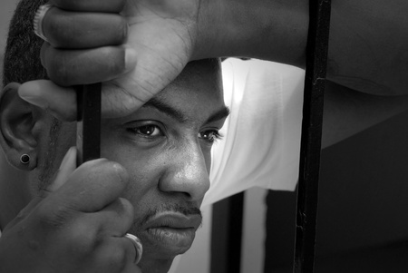 The face of an angry african american male behind iron bars photo