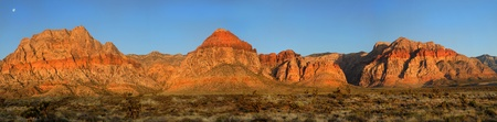 nevada: Dramatic view of Red Rock Canyon in Nevada at sunrise showing the moon still in the sky Stock Photo