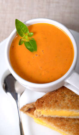 soup bowl: Delicious bowl of homemade tomato soup with a grilled cheese sandwich