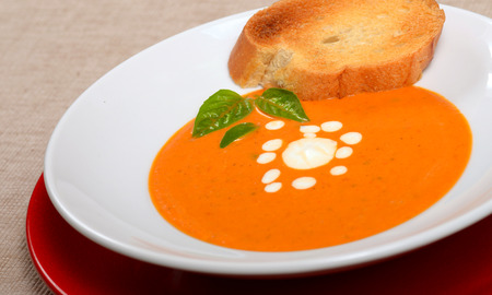 Delicious bowl of homemade tomato soup with grilled bread, basil and sour cream photo