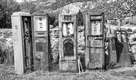 Black and White image of a collection of old rusting gas pumps found in an antique store in New Mexico photo