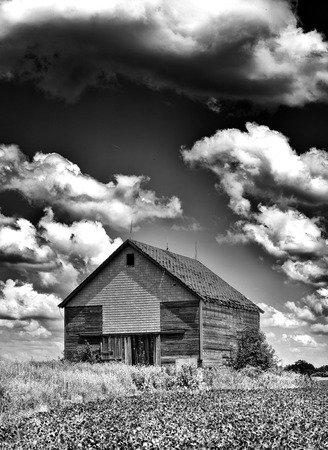 desolate: Spooky old desolate haunted barn with storm clouds overhead like you would see on Halloween in Black and White