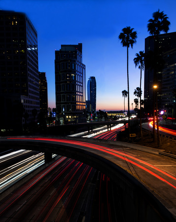 A night scene of a Los Angeles freeway with business buildings in the background take during the blue hour.