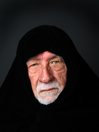 somber: Elder Arab Sheik with a somber expression with a black headdress looking directly into the camera