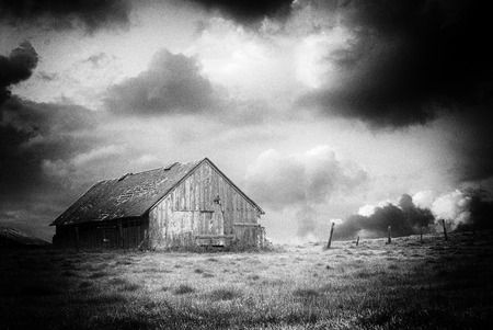 Black and White image of an old abandoned barn on a stormy nights like you would find on Halloween Stock Photo
