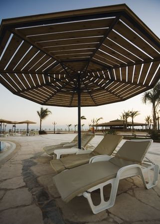 three sunbeds under parasol near the swimming-pool Stock Photo - 650153