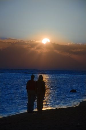a couple meeting sunrise on the beach photo