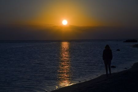 lonely woman watching sunset on the beach photo