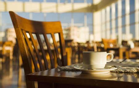 afternoon cafe: Aun-vida positiva de la ma�ana en un caf�. Taza y respaldo de una silla Foto de archivo