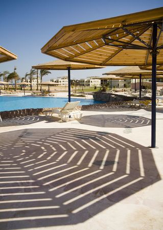 Interior of hotel. Parasols and his striped shadow. Stock Photo - 659585