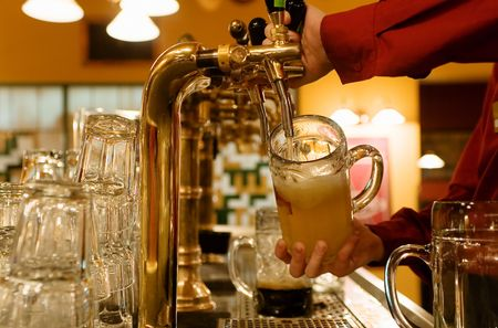 drinks after work: waiting man pouring beer into the glass Stock Photo