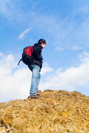 young man climb on top a mountain photo