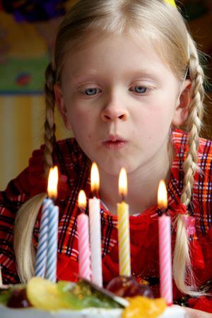 Little girl blowing her birthday candles Stock Photo