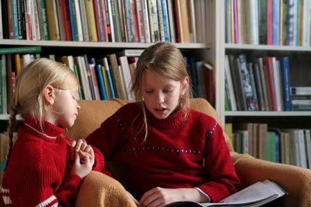 bookish: Two sisters reading together Stock Photo