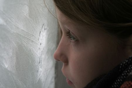 grieve: Young girl looking through the icy window