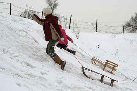 Children pulling her sled photo