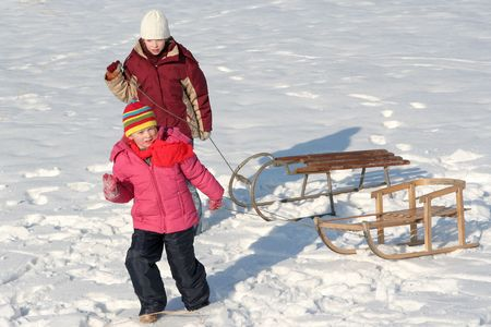 Two girls pulling sleds photo