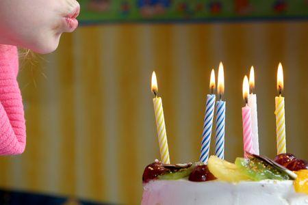 velas de cumpleaños: Niña soplando las velas de cumpleaños